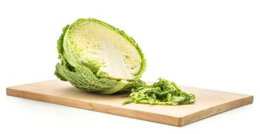 One savoy cabbage half on a chopping board with fresh green chopped leaves isolated on white backgroun