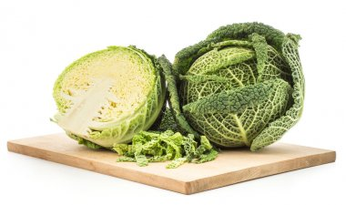 Savoy cabbage on a chopping board isolated on white background one fresh green head one section half and chopped leave