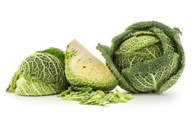Savoy cabbage head and two quarters with chopped leaves stack isolated on white background fresh gree