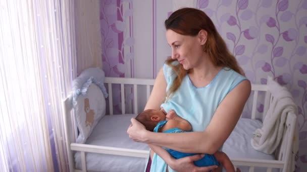 Mladá matka kojení novorozence. Mladá matka kojení novorozence v ložnici dětí