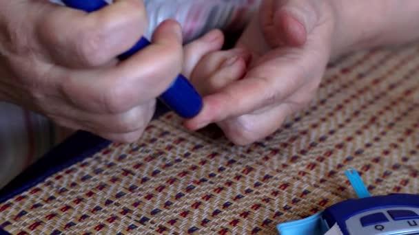 Diabetická zralá žena kontroluje její hladinu glukózy v krvi doma s její domácí monitorování sady glykémie. Měření glukózy v krvi pomocí glukometr