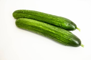 two juicy green cucumbers on a white background close-up