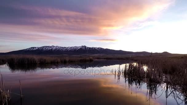 Západ slunce na soumraku na jaře horské jezero - panoramatické sunset do soumraku Časosběr z barevné bouřkové mraky válí přední oblast Skalistých hor a přes jaro jezero tání ledu