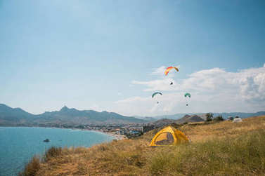 people flying on paragliders at sea