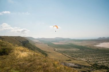 Person flying on paraglider, sky and field on background, Ukraine, Crimea, may 2013 stock vector