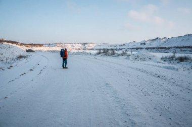 Tourist standing on snowy road in winter mountains, Belarus, Vitebsk stock vector