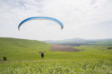 Paraglider flying above field