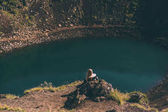 back view of young woman sitting on rock and looking at beautiful crater lake in Iceland