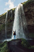 back view of young woman standing with raised hands and looking at beautiful waterfall in Iceland