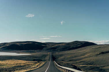 empty asphalt road between scenic hills in Iceland
