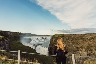 back view of young woman looking at scenic majestic waterfall in Iceland