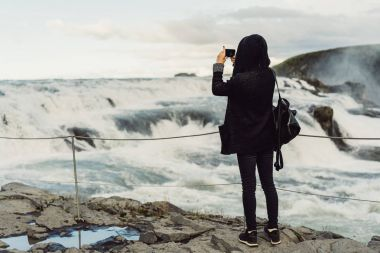back view of young woman photographing majestic waterfall in Iceland
