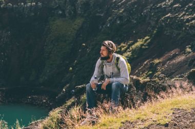 young bearded man sitting on rock and looking at beautiful crater lake in Iceland