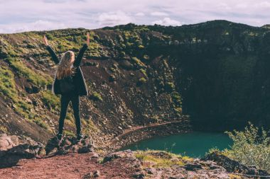 back view of girl standing with raised hands and looking at beautiful crater lake in Iceland