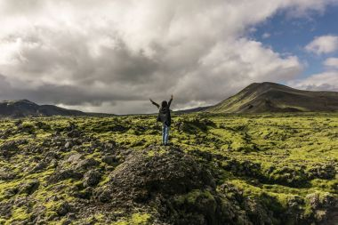 person standing on rock with raised hands and looking at scenic icelandic landscape