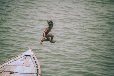 adorable little boy jumping from boat in Varanasi, India