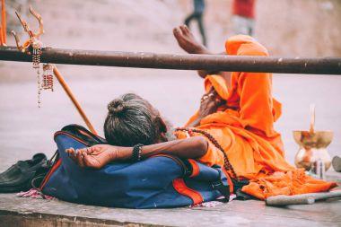 monk in bright orange clothing resting in Varanasi, India