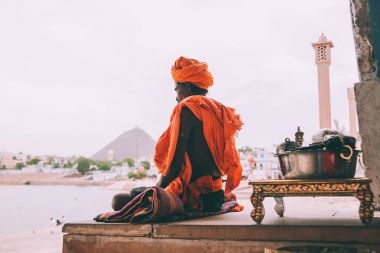 side view of monk in traditional clothing meditating in Rajastan, Pushkar