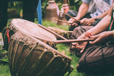 cropped shot of people playing leather drums with sticks in Nepal