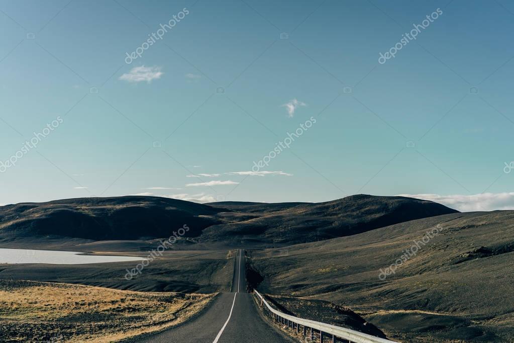empty asphalt road between scenic hills in Iceland