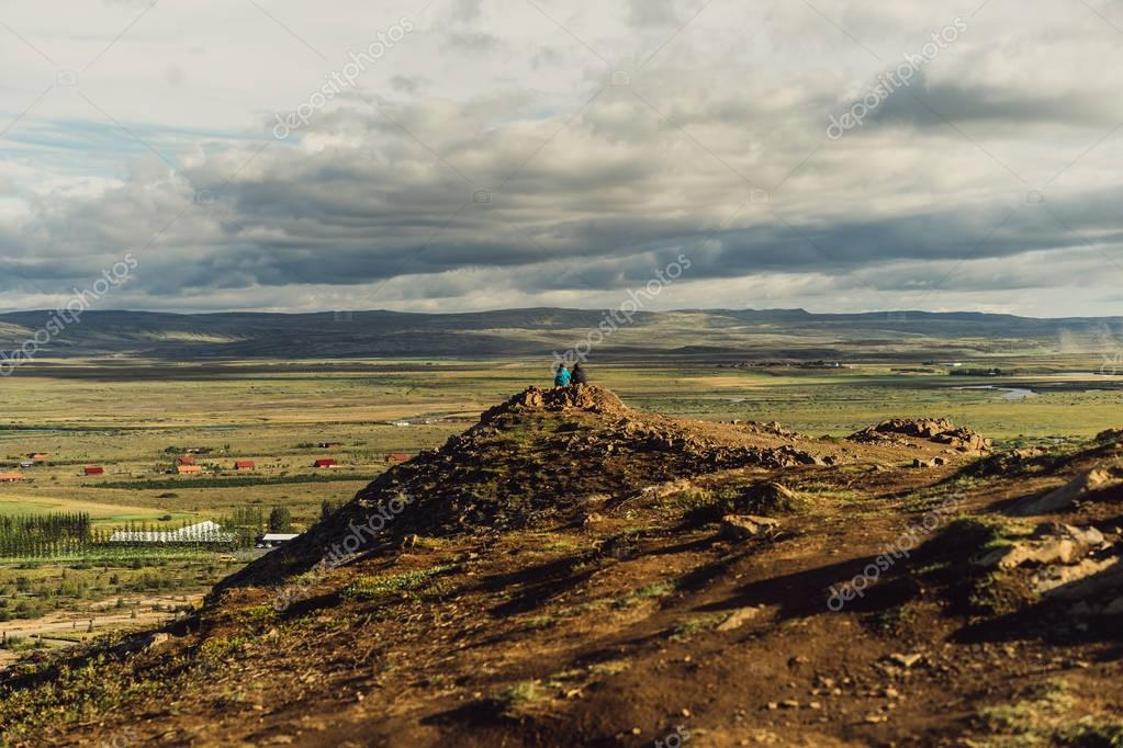 back view of couple sitting on cliff and looking at scenic wild landscape in Iceland