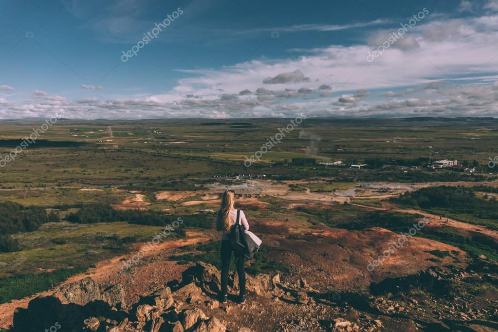 back view of young woman standing on cliff and looking at majestic landscape in Iceland