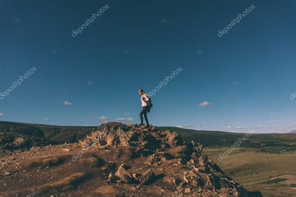 young woman standing on cliff and beautiful landscape in Iceland