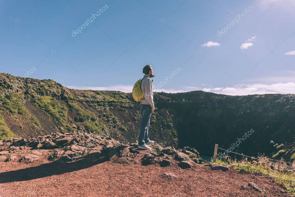 side view of young bearded man with backpack looking at scenic crater lake in Iceland