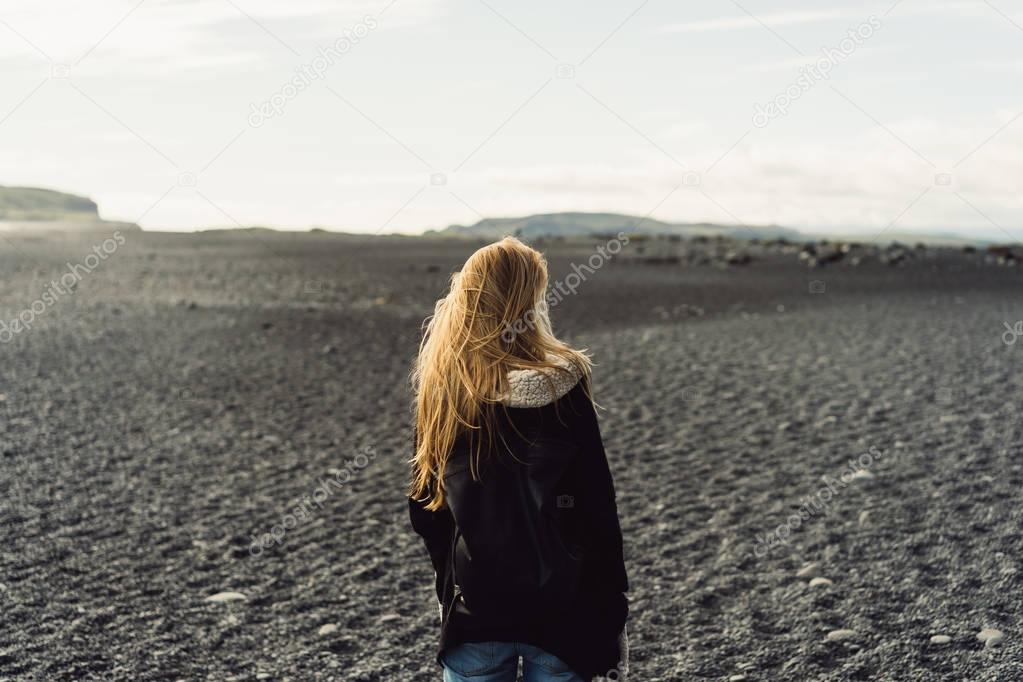 back view of young woman looking at beautiful wild icelandic landscape