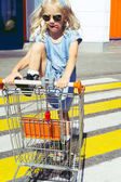 little adorable female child in sunglasses having fun in shopping cart on crosswalk