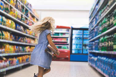 little kid with skateboard standing in supermarket with shelves behind