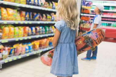 child with skateboard standing in supermarket with shelves behind