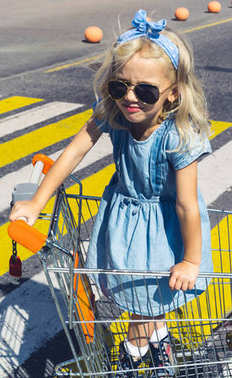 little adorable kid in sunglasses having fun in shopping cart on crosswalk