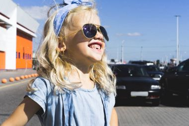 stylish cheerful adorable kid in sunglasses standing on parking with cars
