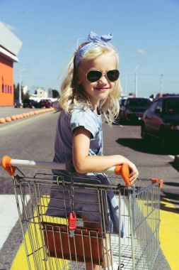 Little child having fun in shopping cart at parking stock vector