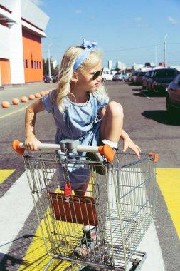 adorable female child having fun in shopping cart at parking