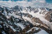 pohled na hory skalnatými vrcholky sněhu pod mraky, Ala Archa národního parku, Kyrgyzstán