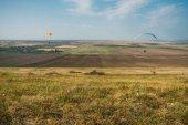 Fotografie Parašutisté klouzání v modré obloze nad malebnou krajinou Krym, Ukrajina, květen 2013