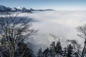 Fotografie malebný pohled zasněžených hor v mlze nedaleko zámku Neuschwanstein, Německo