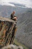 mladý muž sedí na útesu a hledá krásnou krajinu, Altaj, Rusko