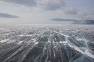 view of ice water surface under cloudy sky during daytime, russia, lake baikal