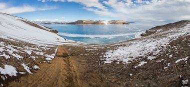 view of sandy shore with ice on water surface,russia, lake baikal