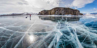 male hiker with backpack standing on ice water surface against rock formation on shore ,russia, lake baikal