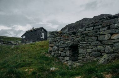 ruined old stone wall and rural house on background over field with green grass, Norway, Hardangervidda National Park