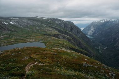 view of hill slope with grass and small pond, mountains on background, Norway, Hardangervidda National Park