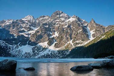 view of snow covered mountain peaks over lake water, Morskie Oko, Sea Eye, Tatra National Park, Poland