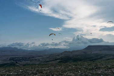 Parachutists gliding in blue sky over scenic landscape of Crimea, Ukraine, May 2013