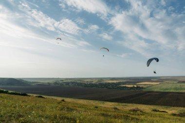 Parachutists gliding in blue sky over scenic landscape of Crimea, Ukraine, May 2013 stock vector