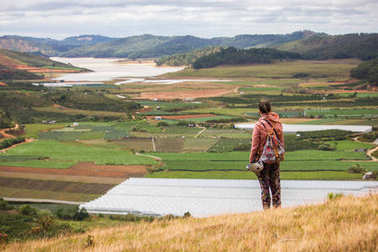 back view of man looking at beautiful landscape with agricultural fields and mountains, vietnam, dalat region