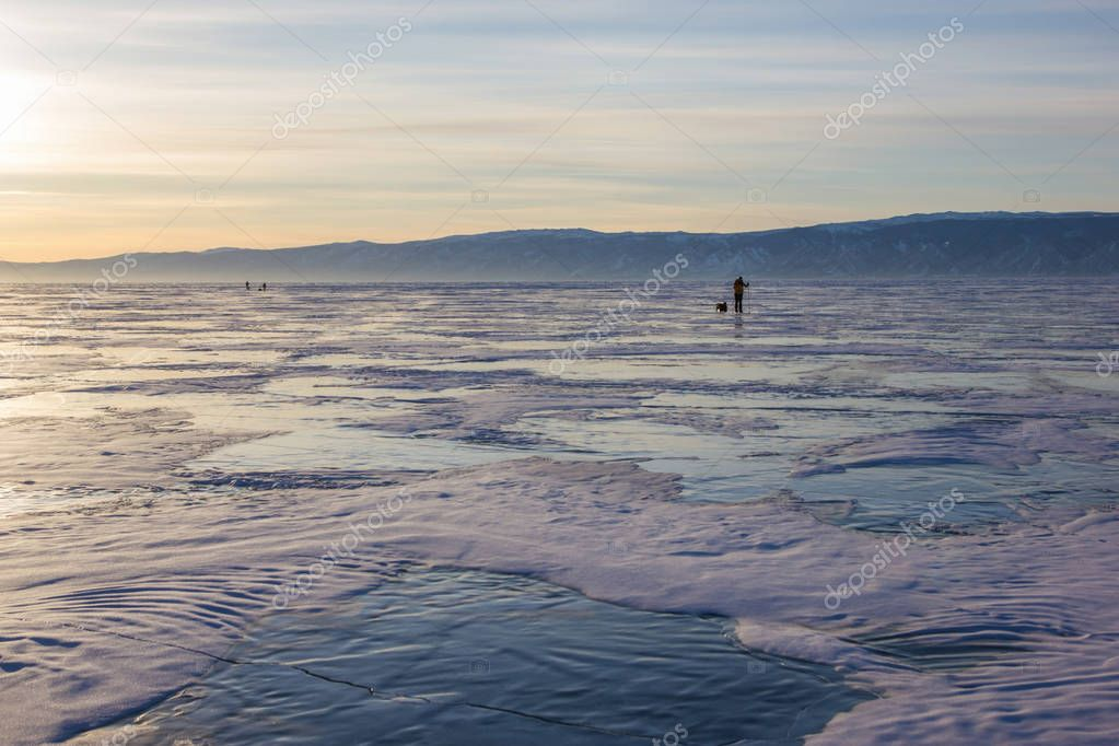 male hiker with backpack walking on ice water surface against hills on shore,russia, lake baikal
